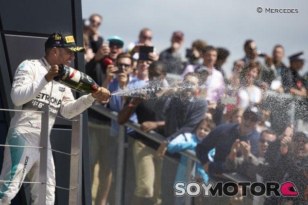 Lewis Hamilton disfrutando con el champán en el podio de Silverstone - LaF1