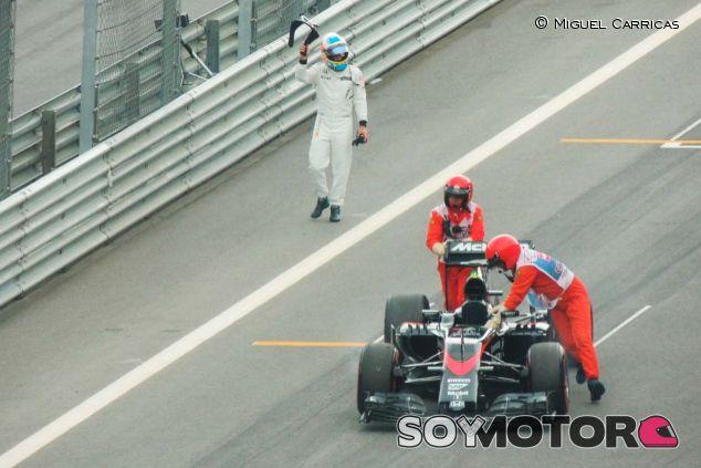 Fernando Alonso saluda  a la afición mientras los comisarios empujan su McLaren - LaF1