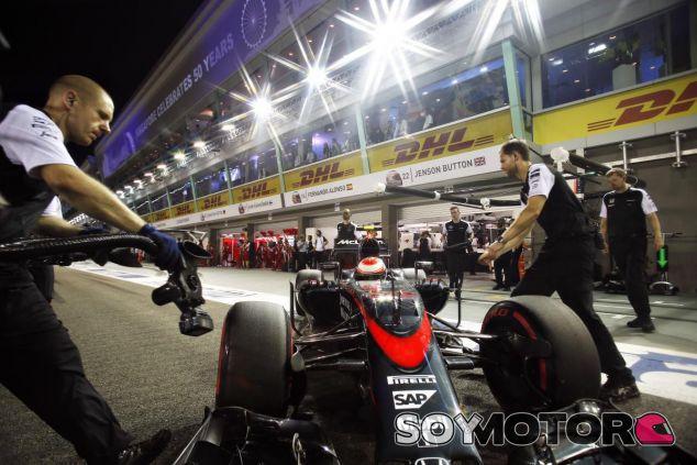 Los mecánicos de McLaren llevando el coche de Button de vuelta al box - LaF1