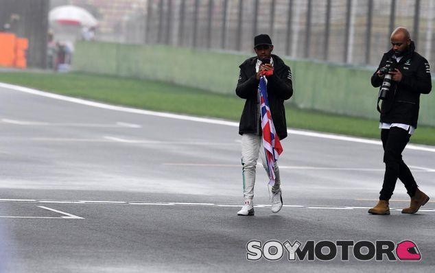 Lewis Hamilton cruza la recta principal tras repartir gorras firmadas entre los fans - SoyMotor