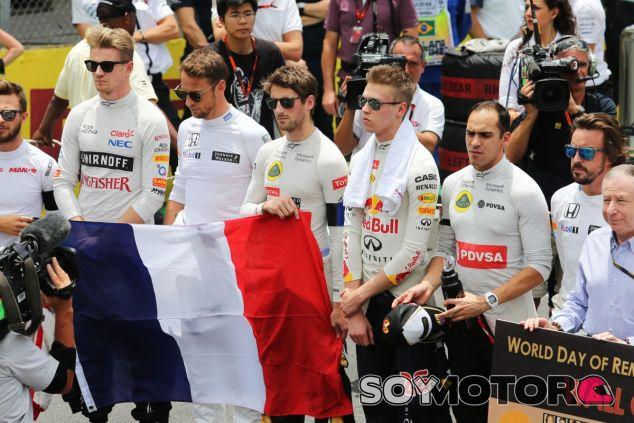 Grosjean sostiene la bandera francesa mientras los pilotos guardaban un minuto de silencio en Brasil - LaF1