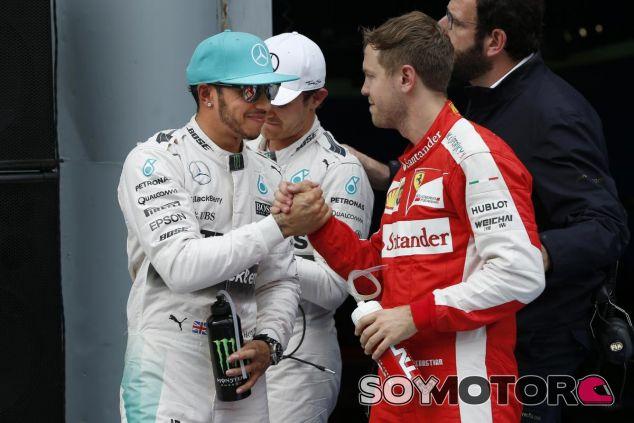 Lewis Hamilton y Sebastian Vettel saludándose en uno de sus podios - LaF1