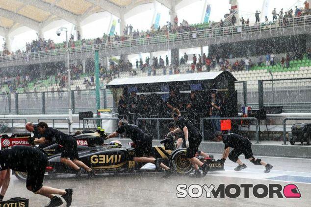 Los mecánicos meten a Maldonado en el garaje de Lotus bajo una intensa lluvia - LaF1