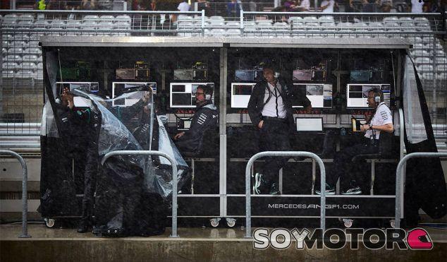 El personal de Mercedes intenta salvaguardar su pit-wall de la lluvia - LaF1