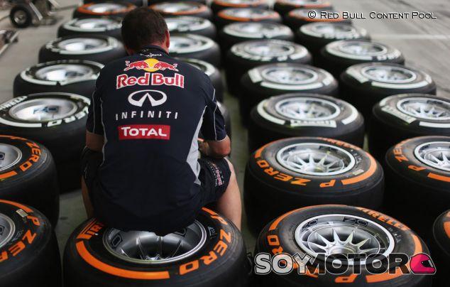 Un miembro del equipo Red Bull se sienta sobre los neumáticos Pirelli - LaF1