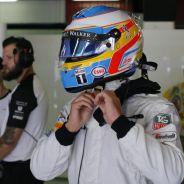 Fernando Alonso abrochándose el casco en el box de McLaren - LaF1