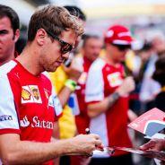 Vettel firmando autógrafos a algunos aficionados durante el GP de Brasil - LaF1