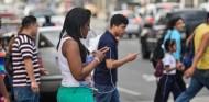 Gente cruza la calle mientras usa su teléfono móvil - SoyMotor.com