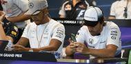 Lewis Hamilton (izq.) y Fernando Alonso (der.) con sus móviles – SoyMotor.com
