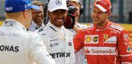 Valtteri Bottas (gorra azul, de espaldas) habla con Lewis Hamilton (izq.) y Sebastian Vettel (der.) –SoyMotor.com
