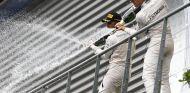Hamilton y Rosberg regando de champán a sus mecánicos desde el podio de Spa - LaF1