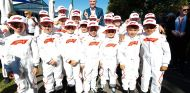 Niños de parrilla posan con el director comercial de la Fórmula 1, Sean Bratches, en Australia - SoyMotor.com