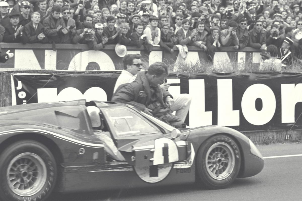 Foyt pilota hacia la línea de meta mientras Gurney está sentado en el capó - Le Mans, Francia, 1967